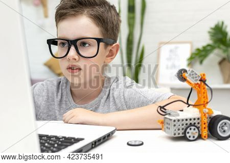 Clever Boy In Eyeglasses Builds And Programs A Robot Car Using A Laptop At Home. The Child Is Learni