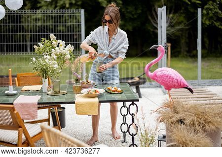 Young Woman Serving With Food Dining Table At The Backyard Of Her House. Beauty And Aesthetics In Ev