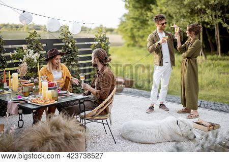 A Group Of Young Friends Having Great Summertime, Dining And Talking At Backyard Of The Country Hous