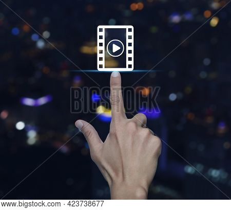 Hand Pressing Play Button With Movie Flat Icon Over Blur Colorful Night Light Modern City Tower And