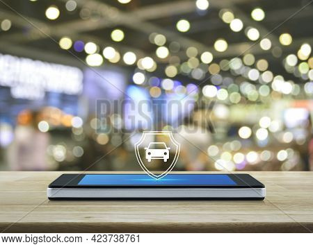 Car With Shield Flat Icon On Modern Smart Mobile Phone Screen On Wooden Table Over Blur Light And Sh