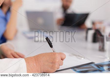 Closeup Of Physician Senior Woman Writing Sickness Treatment On Clipboard Prescribing Healthcare Pil