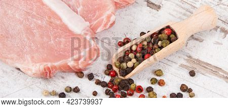 Fresh Raw Loin With Pepper On Wooden Spoon For Cooking Lunch Or Dinner