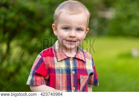 Happy Boy Child Is Smiling And Enjoying His Life. Portrait Of Young Boy In The Park Or Outdoors. Con
