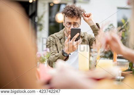 Self Lover Guy Looking At Himself On Phone While Dining With Friends Outdoors. Stylish Man On A Fest