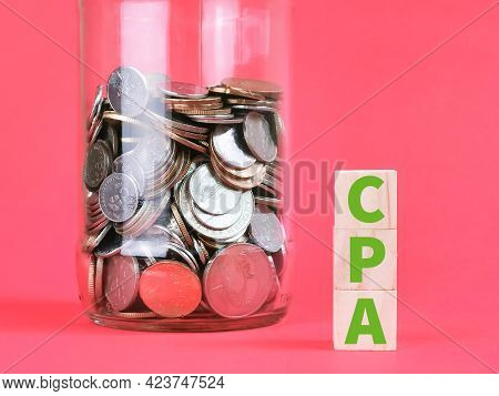 Cost Per Action Concept. Text Cpa On Wooden Cubes With Coins Against Red Background.