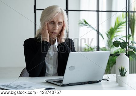Tired Elderly Businesswoman, Suffering From Eye Strain, After Working On A Laptop In The Office