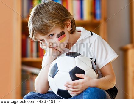 Sad And Not Happy Little Kid With Football About Lost Football Or Soccer Game. Child After Watching