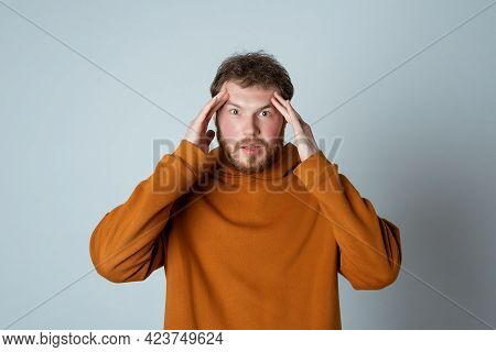 Troubled And Anxious Bearded Young Man Cover His Head With Hands And Looking Worried, Panicking, Sta
