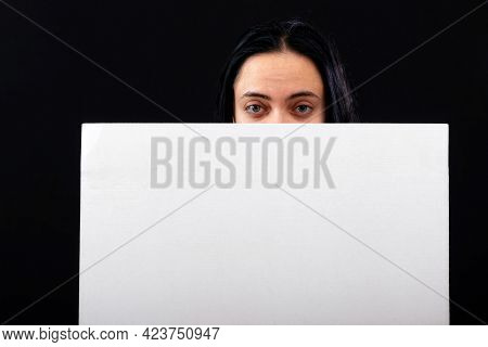 Attractive Dark Haired Woman Looking Over White Blank Poster, Isolated On Dark Background