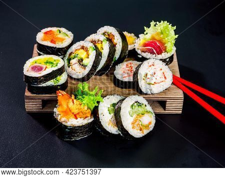 Set Of Sushi Rolls On Wooden Board On Black Background. Different Kind Of Maki Sushi Roll With Tuna,