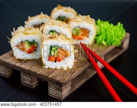 Katsuobushi Uramaki Sushi Roll With Salmon And Cucumber On Wooden Board On Black Background. Sushi R