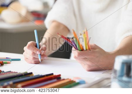 Woman Drawing With Multicolored Pencils On White Sheet Of Paper Closeup