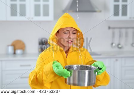 Young Woman In Raincoat Collecting Leaking Water From Ceiling At Home. Time To Call Roof Repair Serv