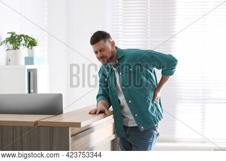 Man Suffering From Back Pain In Office. Bad Posture Problem