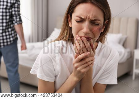 Scared Woman With Injuries And Abuser In Bedroom. Domestic Violence Victim
