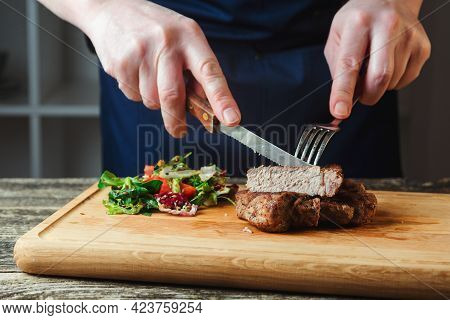 Chef Cutting Grilled Beef Steak On Wooden Board. Juicy Grilled Beef Steak With Spices On Cutting Boa