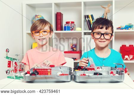 Clever Children Creating Diy Construction At The Table. Happy Boys Playing With Metal Constructor. E