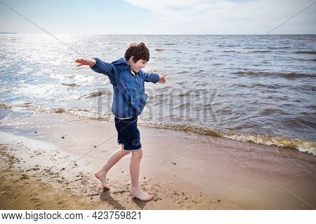 Boy In Blue Jacket And Shorts Barefoot Running On Sand On The Seashore, Sunny Day, Vignetted