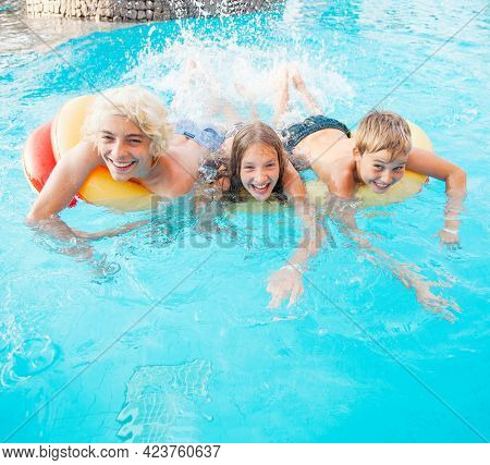 Teens play fun with splashes on the side of the pool at the resort Children Having Fun In Outdoor Swimming Pool. Boy and girl in summer vacation