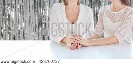 homosexuality, same-sex marriage and lgbt concept - close up of happy married lesbian couple hands on wedding over foil party curtain on background