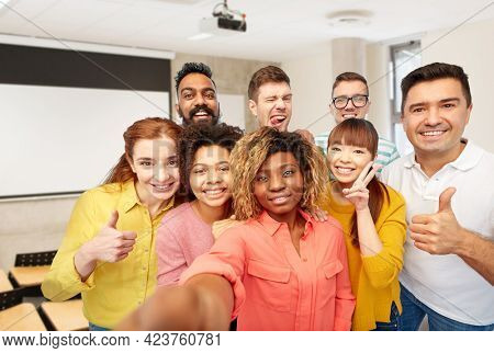 diversity, education and school concept - group of smiling international university students and teacher taking selfie over lecture hall on background