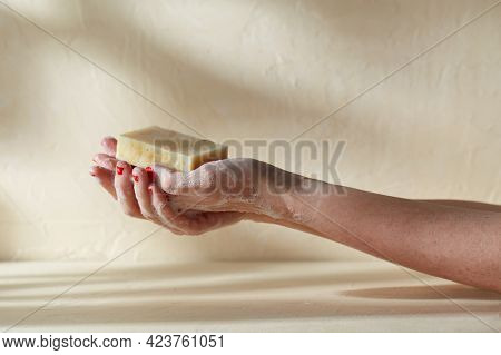 natural cosmetics, hygiene and beauty concept - foamy hands holding bar of craft soap on beige background