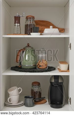 Manual Coffee Grinder And Other Appliances On Shelving Unit In Kitchen
