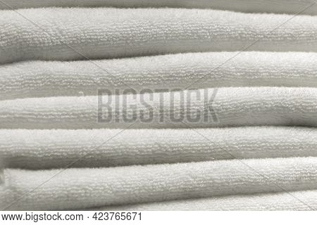 A Stack Of Carelessly Lying White Towels, Texture Background. Home Cleanliness Hygiene And Comfort