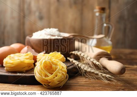 Uncooked Homemade Pasta And Ingredients On Wooden Table. Space For Text
