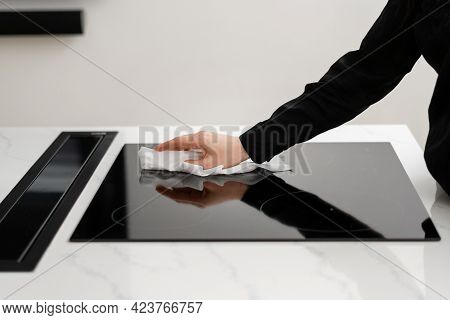 Woman Cleaning Black Reflective Glass Induction Stove With White Rag, Making Surface Shiny And Clean