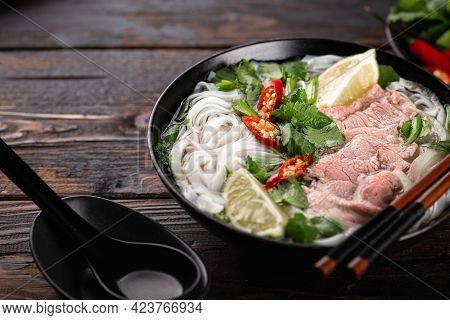 Pho Bo Vietnamese Soup With Beef And Noodles On A Wooden Background, Selective Focus