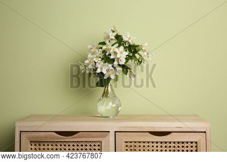 Bouquet Of Beautiful Jasmine Flowers In Vase On Wooden Commode Near Light Green Wall
