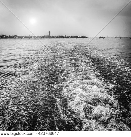 The lagoon view from a boat taxi leaving behind it Venice, Black and white photography