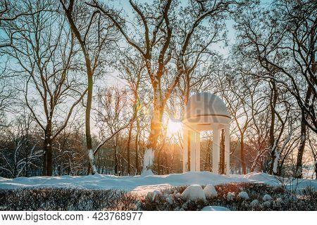 Gomel, Belarus. Winter City Park. Sun At Sunset Shining Through Gazebo In City Park. Garden Pergola