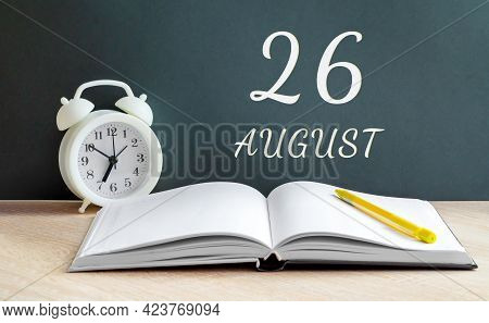 August 26. 26-th Day Of The Month, Calendar Date.a White Alarm Clock, An Open Notebook With Blank Pa