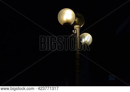 Glowing Street Lamp Glass Balls In A Very Dark Night.