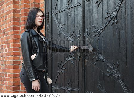 Young Beautiful Brunette Girl In Black Jacket And Jeans Stands Near Door Of Gothic Church On Summer