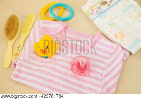 Baby Care Accessories And Clothes On Background Of Changing Table Top View.