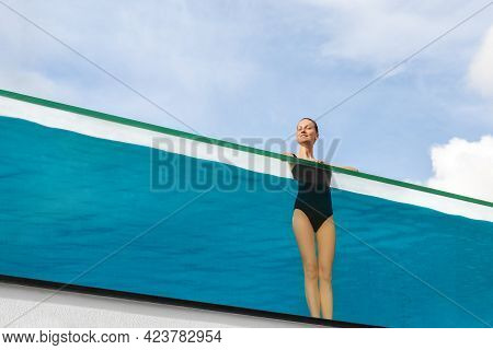 Young Adult Caucasian Sporty Slim Smiling Relaxing Woman Enjoy Stand In Pool With Clear Blue Water A