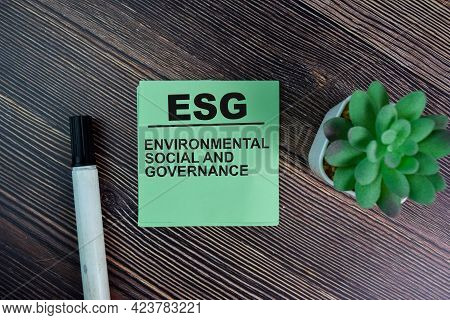 Esg - Environmental Social And Governance Write On Sticky Notes Isolated On Wooden Table.