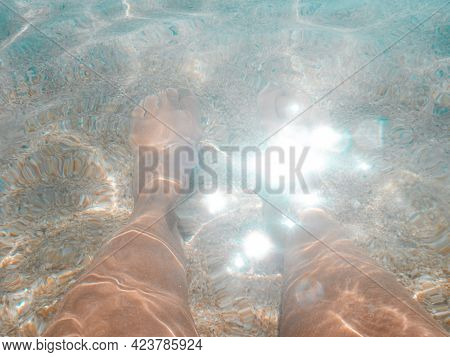 Vacation At Sea. Turquoise Clear Water, Sand, Reflection Of The Sun's Rays. Female Feet Close Up In