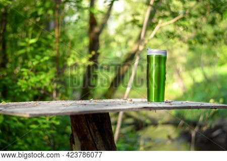 Green Stainless Steel Cup, Mug With Thermos Stands On A Wooden Table In The Forest On A Green Natura