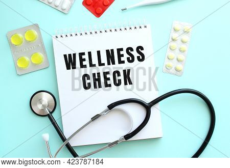 The Text Wellness Check Is Written On A White Notepad That Lies Next To The Stethoscope And Pills On