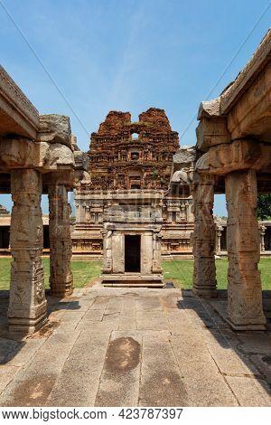 Mandapa (pillared outdoor hall) and gopura (tower) in Achyutaraya Temple. Ruins in Hampi, Karnataka, India