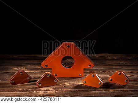 A Set Of Orange Magnetic Corners For Welding Metal Structures With A Fixed Angle Value. Studio Photo