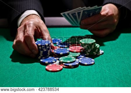 Playing poker in a casino holding winning hand of cards and betting all gambling chips concept for gambling, betting and winning