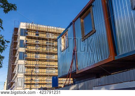 Construction Trailer As Temporary Housing For Builders Against The Background Of An Apartment Buildi