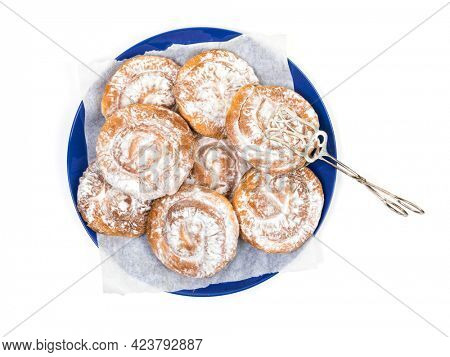 Typical spiral Ensaimadas pastry from the Balearic island of Mallorca, Spain and pastry tongs on a plate Isolated on white background, high angle view