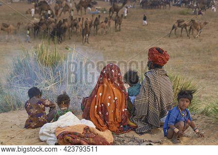 Pushkar, Rajasthan, India - November 5, 2008: Family Group Around An Open Fire After A Night Sleepin